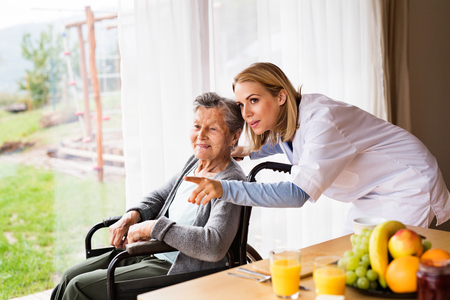 Gesundheitsbesucher und eine ältere Frau während des Hausbesuchs.