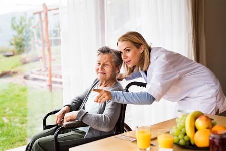 Visiteur de santé et une femme âgée lors d'une visite à domicile.