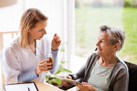 Health visitor and a senior woman with tablet. Banco de Imagens - 88089805