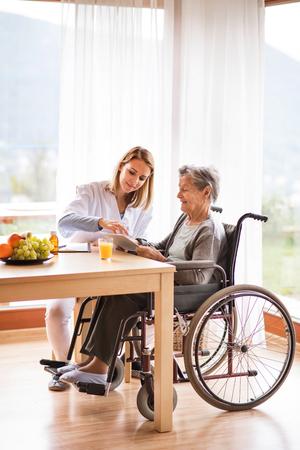 Visitante de salud y una mujer mayor con tableta. Foto de archivo