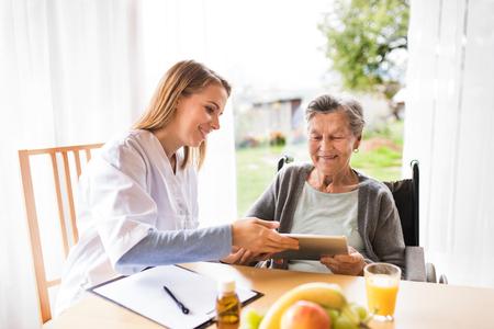 visitante de salud y una mujer mayor con la tablilla Foto de archivo
