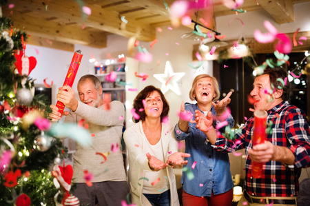 Senior friends with confetti poppers next to Christmas tree.