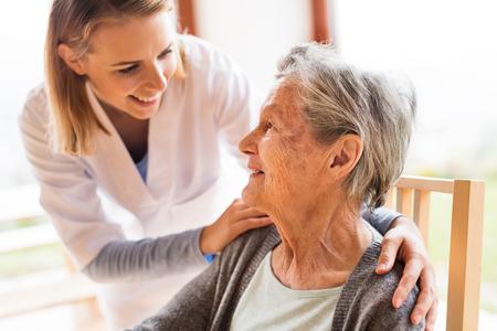 健康の訪問者と家の間に年配の女性を参照してください。