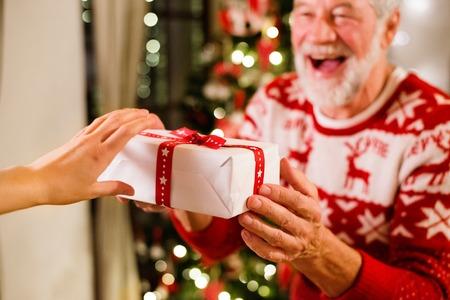 Starszy mężczyzna przed choinką trzyma prezent.