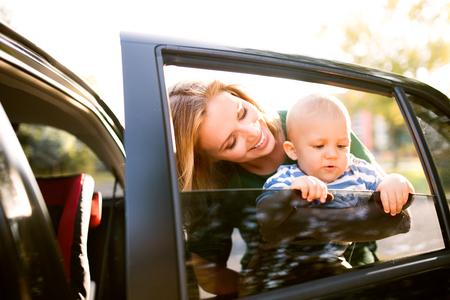 彼女の小さな男の子と車のそばに立っている若い母親。 写真素材