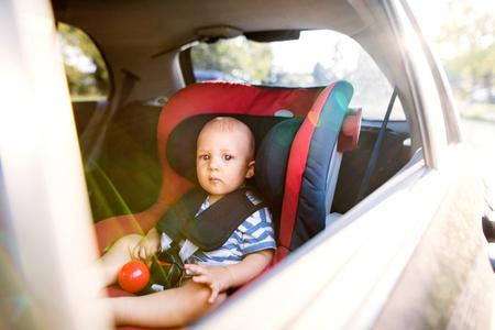 cinturon seguridad: Little baby boy sitting in the car seat in the car.
