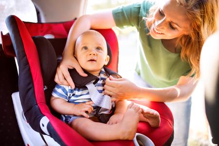 젊은 어머니가 자동차 좌석에 아기 소년 퍼팅.