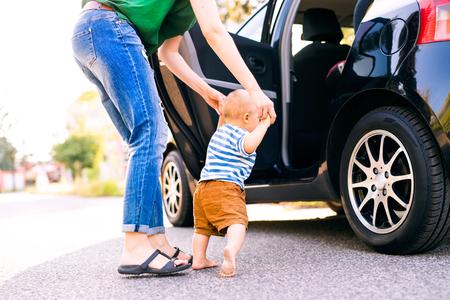 Junge Mutter mit ihrem kleinen Baby , das durch das Auto geht Standard-Bild - 88136760