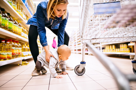 Young mother with her little baby boy at the supermarket. Reklamní fotografie - 88121586