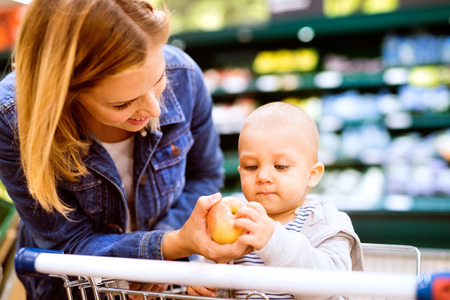 Junge Mutter mit ihrem kleinen Baby am Supermarkt.