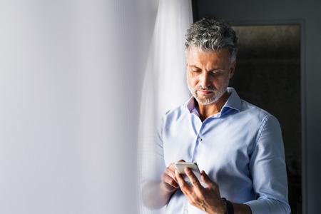Rijpe zakenman met smartphone in een hotelruimte.