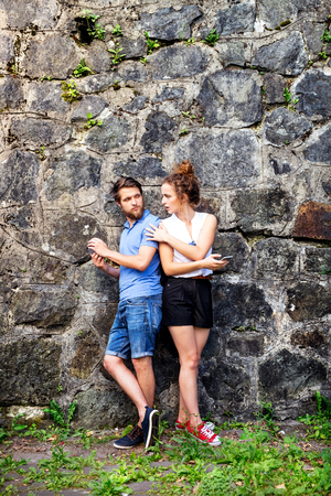 Young couple with smartphones against stone wall in town. Reklamní fotografie