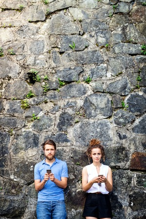 Young couple with smartphones against stone wall in town. Stock Photo