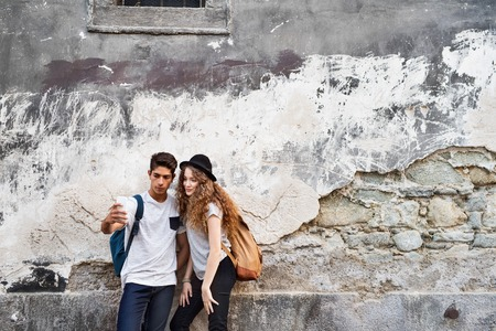 Two young tourists with smartphone and camera.