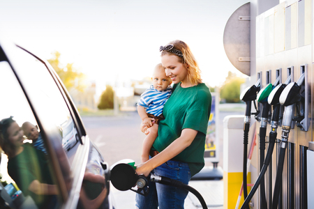 Young mother with baby boy at the petrol station.