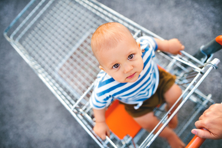 Baby boy sitting in the shopping trolley outside. Reklamní fotografie - 88335533
