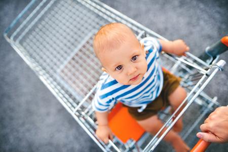 De jongenszitting van de baby in het het winkelen karretje buiten.