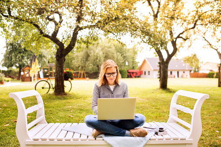 Young woman with a laptop studying outdoors. Stock Photo