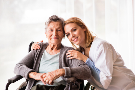 Visitante de salud y una mujer mayor durante la visita domiciliaria.