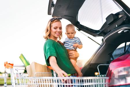 아기 소년 차에 쇼핑을 가하고 어머니.