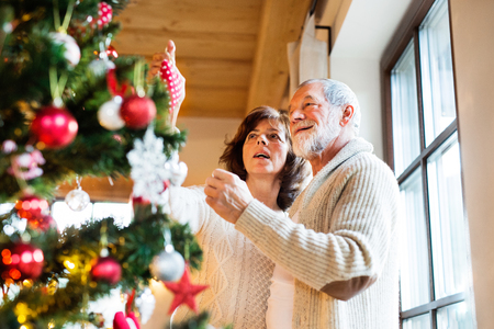 ball and chain: Senior couple decorating Christmas tree at home. Stock Photo