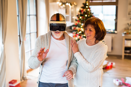 Senior couple in front of Christmas tree with VR goggles.