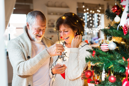 Senior couple at home decorating Christmas tree. Imagens - 88414453