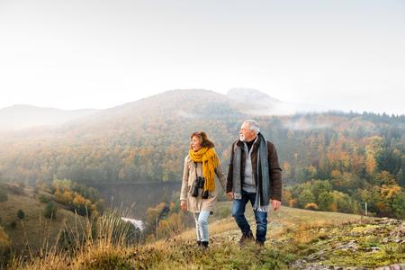 Senior pareja en un paseo en una naturaleza de otoño. Foto de archivo