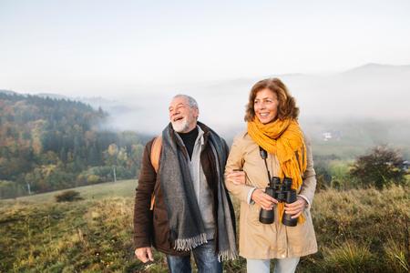 Senior couple on a walk in an autumn nature. 免版税图像