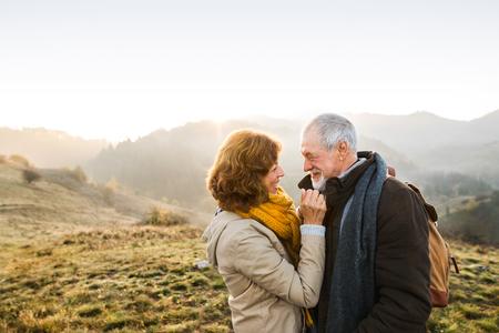 Senior couple on a walk in an autumn nature. Foto de archivo