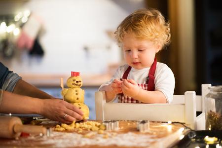 De jongen die van de peuter peperkoekkoekjes thuis maakt. Stockfoto - 88414523