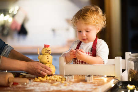 Toddler boy making gingerbread cookies at home. Stock Photo