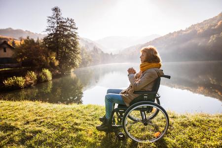 Hogere vrouw in een rolstoel in de herfstaard.