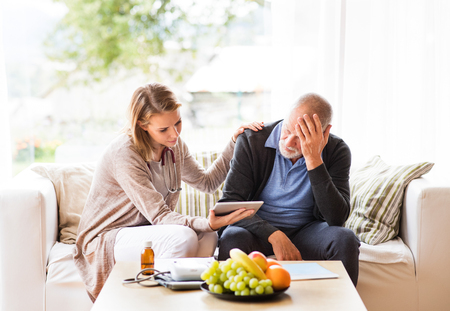 Health visitor and a senior man with tablet during home visit. Stock fotó