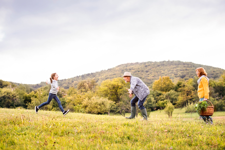 Senior couple with grandaughter in nature.