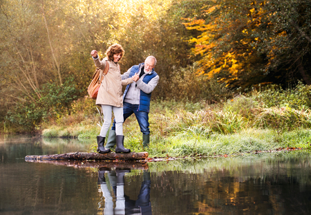 秋の自然の中の散歩に年配のカップル。