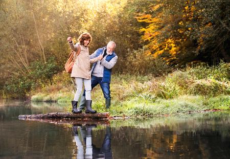 Senior couple on a walk in autumn nature. 스톡 콘텐츠