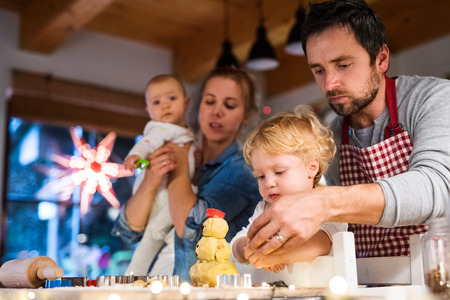 Young family making cookies at home. Archivio Fotografico