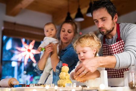 Jonge familie die koekjes thuis maakt. Stockfoto