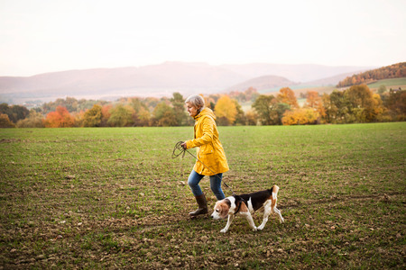 Senior woman with dog on a walk in an autumn nature.