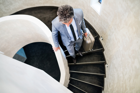 Businessman with suitcase walking down the stairs.