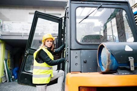 Vrouwelijke vorkheftruckchauffeur buiten een pakhuis.