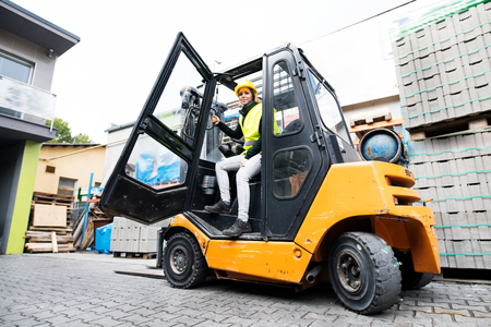Female forklift truck driver outside a warehouse. Stock Photo - 89199714