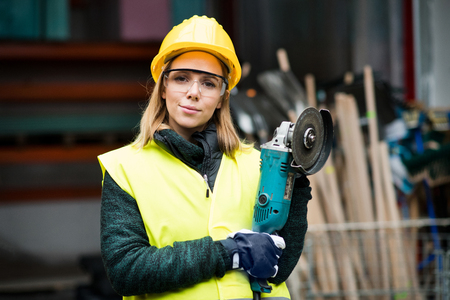Female worker with angle grinder in a warehouse. Stock Photo