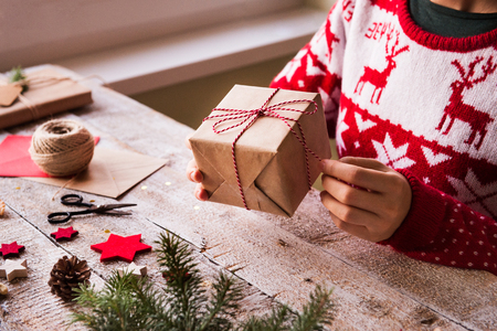 Nerozpoznatelná žena zabalí vánoční dárek. Reklamní fotografie