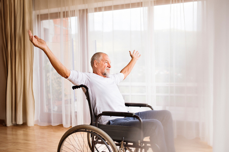 Senior man sitting on wheelchair at home.