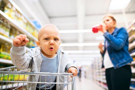 Jonge moeder met haar kleine babyjongen bij de supermarkt.