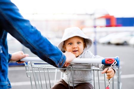 駐車場で男の子と一緒に、買い物に行く母親。
