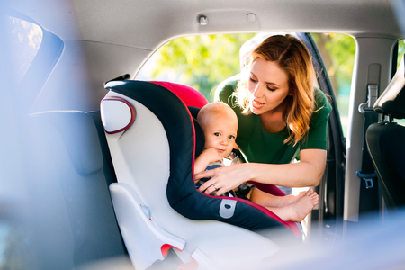 Young mother putting baby boy in the car seat. Standard-Bild