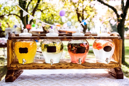 Jars with a tap on a wooden stand in a garden. Stock Photo